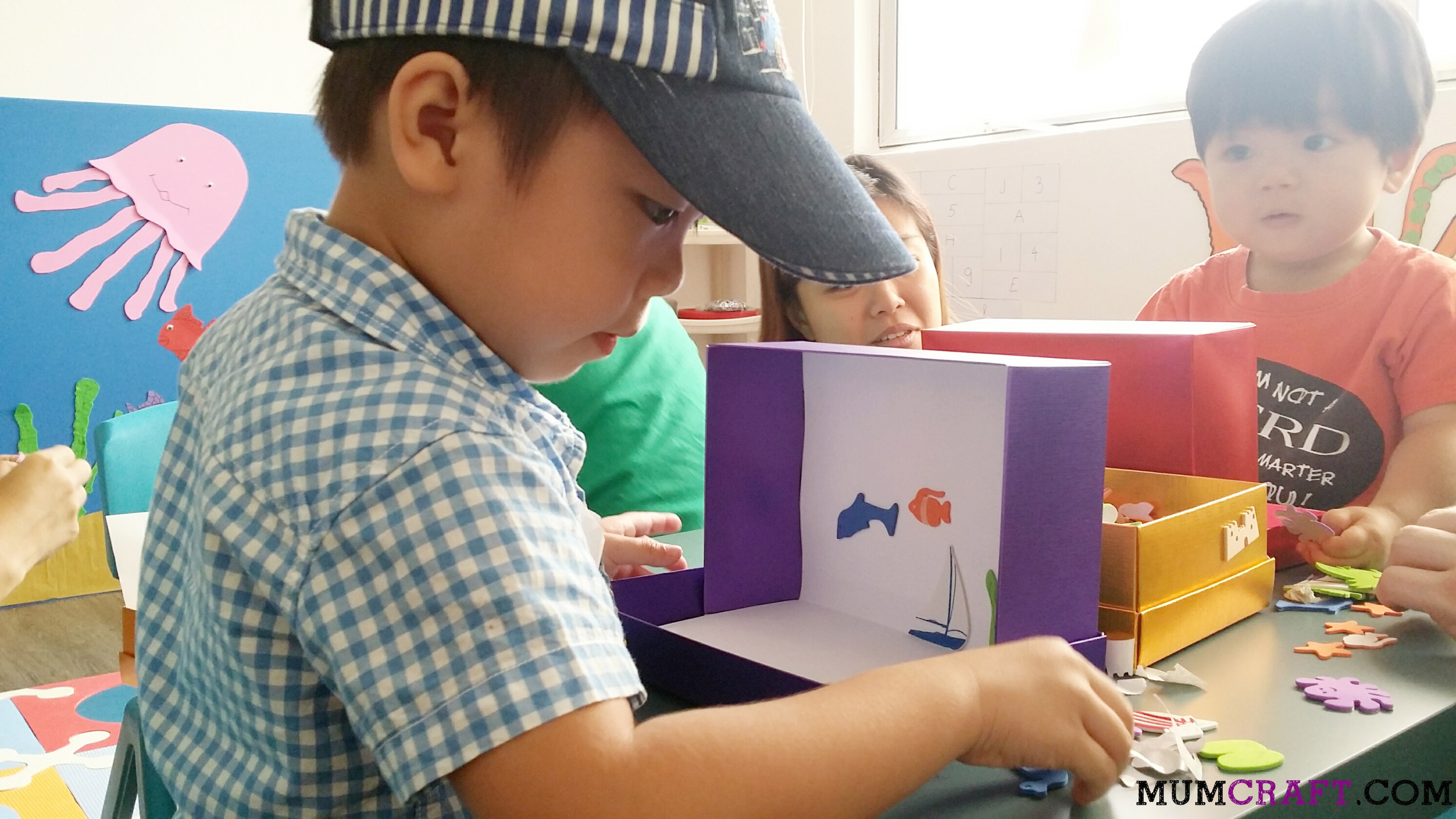 Making his own aquarium with foam stickers.